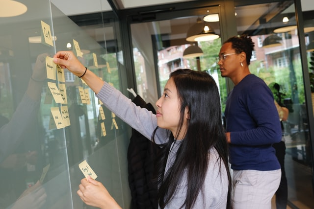 People with post-it notes on glass  screen