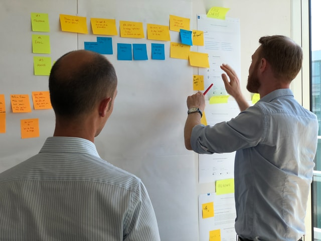 Two people working with post-it notes - small